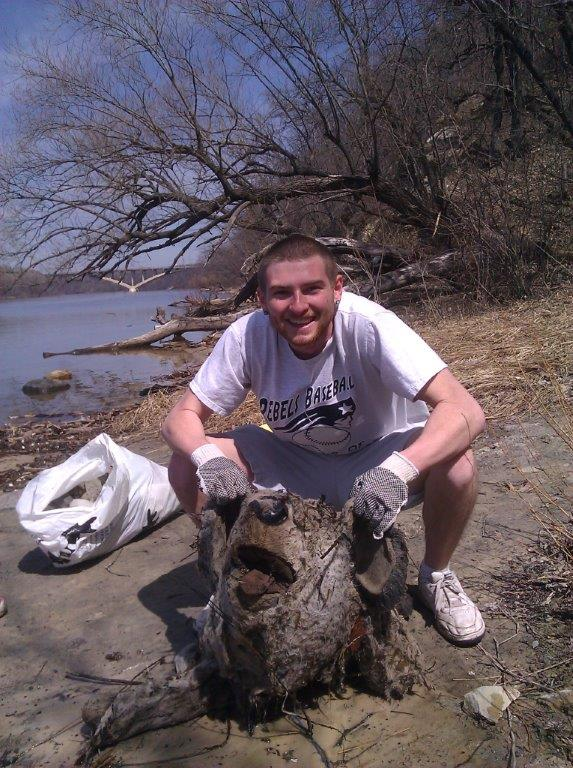 A volunteer poses with a severed stuffed bear found along the Mississippi River last year.