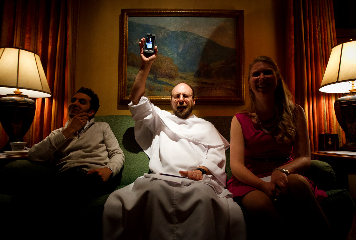 """Chemistry professor Father Patrick Tobin raises his cell phone in mock concert behavior as students sing karaoke during a Catholic Studies """"Monte Casino Night"""" Feb. 22 in Sitzmann Hall. (Photo by Mike Ekern '02)"""