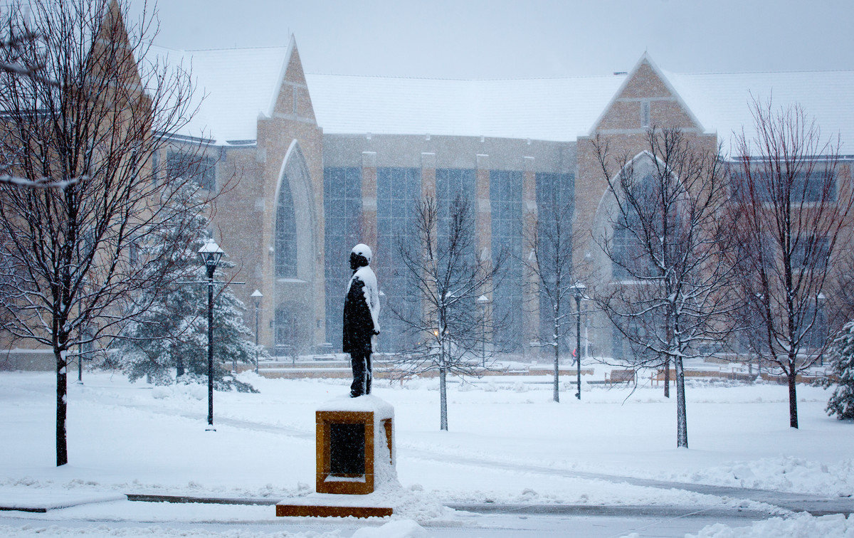 The statue of John Ireland stands amid falling snow on the lower quad April 11. (Photo by Mike Ekern '02)