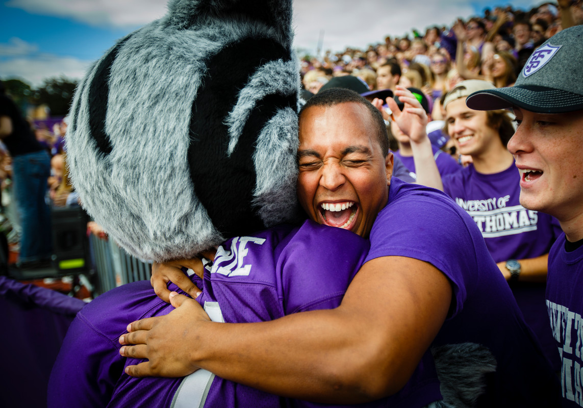 A student gives Tommie the mascot a hug during the Tommie-Johnnie football game Sept. 21 in O'Shaughnessy Stadium. St. Thomas lost to Saint John's 18-20. (Photo by Mike Ekern '02)