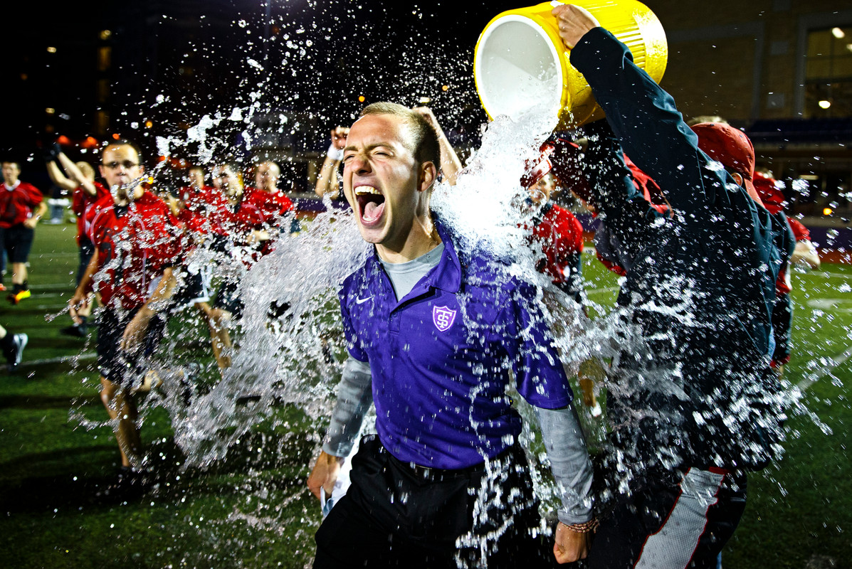 """St. John Vianney head coach Nathanial Binversie gets a victory shower from his team during the 14th annual Rectors' Bowl on Sept 28 in O'Shaughnessy Stadium. The annual tradition, in which the graduate St. Paul Seminary """"Sons of Thunder"""" take on the undergraduate SJV seminary """"JAXX"""", saw the undergrads take the cup 19-12. (Photo by Mike Ekern '02)"""