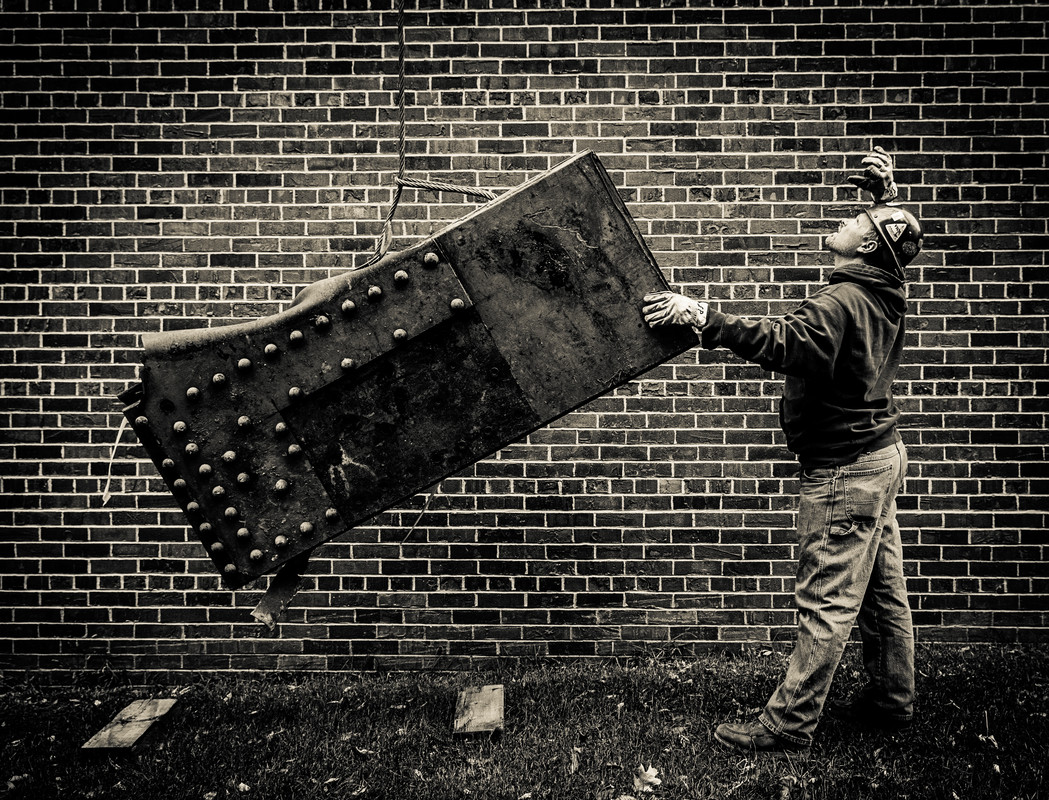 A worker lowers a piece of 35W bridge debris into its temporary holding location behind Brady Education Center. School of Engineering dean Don Weinkauf secured three pieces of the fallen 35W bridge for St. Thomas. They will eventually be displayed near the Frey Science and Engineering Center where they will be involved in a ceremony for graduating engineering students. (Photo by Mike Ekern '02)