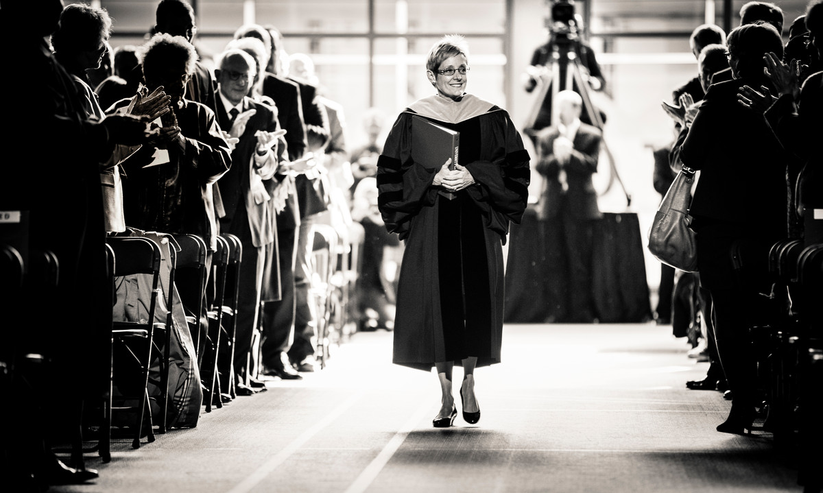 President Julie Sullivan walks past an applauding audience as she processes into the Anderson Athletic and Recreation Complex field house during her inauguration as the 15th president of St. Thomas on Oct. 17. (Photo by Mike Ekern '02)