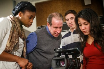 Professor Timothy Scully, second from left, and students look over a video camera during a video production class.