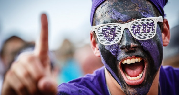 A student cheers for St. Thomas at the Tommie Johnnie football game.