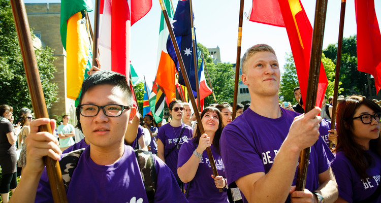 International students carry flags and walk during the annual March Through the Arches ceremony on September 2, 2014.