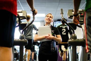Student instructor Sophie Gottsman (Exercise Science) talks with seminarians working out on elliptical machines during a Fit for Ministry class in the Anderson Athletic and Recreation complex on November 17, 2014. The course, specifically designed for seminarians from The Saint Paul Seminary School of Divinity, aims to provide physical direction for students focused on primarily intellectual studies. The class is the culmination of a collaboration between the school of divinity and the Health and Human Performance Department.