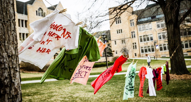 """T-shirts representing women affected by sexual assault or violence hang from a line in the lower quad April 21, 2015. The """"Clothesline Project"""" display was part of a week-long collection of activities meant to highlight and combat rape culture on college campuses. The display was put on by student group Feminist Community (FemCom), a group run out of the Luann Dummer Center for Women."""