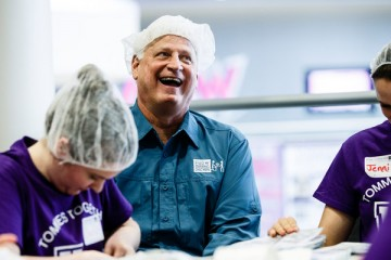 Feed My Starving Children executive director and alum Mark Crea '78 laughs with volunteers during the St. Thomas Day of Service mobile pack event May 6, 2015 in the Anderson Student Center's Campus Way. Feed My Starving Children brought mobile supplies to St. Thomas where faculty, staff and student volunteers packed thousands of meals for children without food overseas.
