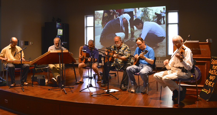Father David Smith (right) plays his violin as part of a Justice and Peace Studies celebration. The department has been at St. Thomas for 30 years. (Photo provided)
