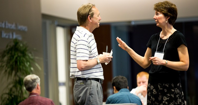 Erika Scheurer, associate professor of English and director of the Writing Across the Curriculum program, right, talks with Chris Anson, a distinguished professor at North Carolina University and Writing Across the Curriculum expert, left, at a Writing Across the Curriculum seminar.