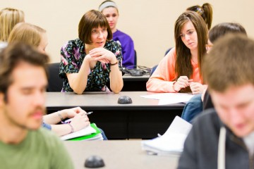 Professor Sherry Jordan (center, wearing floral dress) talks with students during a combined English and Theology course in a McNeely Hall classroom. The course is part of the Writing Across the Curriculum faculty development initiative.