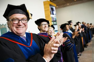 Dr. Donald Weinkauf, dean of the School of Engineering, and other faculty applaud for students at the 2014 undergraduate commencement ceremony on May 24, 2014, at the Minneapolis Convention Center.