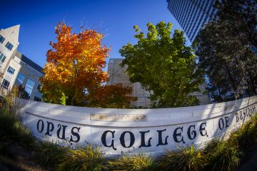 "Schulze Hall and a tree with colorful leaves are pictured with the ""Opus College of Business"" sign and downtown skyscraper on a fall day in Minneapolis on October 10, 2014."