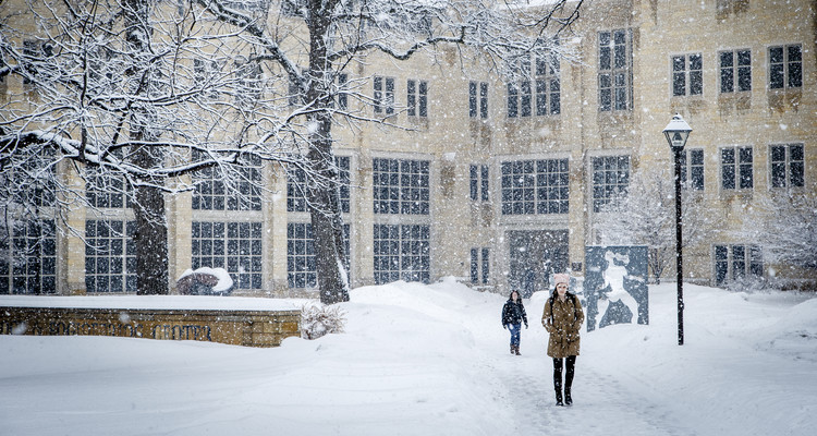 Students walk through the snow across Sabo Plaza on South Campus in front of Owens Science Hall and O'Shaughnessy Science Hall during a snow storm on February 20, 2014 in St. Paul.