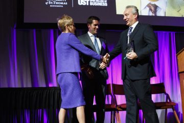 Luigi Bernardi ('85, MBA) receives the John F. Cade Award for outstanding achievement as an entrepreneur from UST President Dr. Julie Sullivan during the 2015 Entrepreneurship Awards gala in the Schulze Grand Atrium in the School of Law building in downtown Minneapolis on November 19, 2015. Bernardi is president of Aurora Investments LLC, a real estate firm based in Edina. Standing in the background is Michael L. Reger ('00 MBA) president and CEO of Norther Oil & Gas, Inc, and 2014 recipient of the John F. Cade Award.