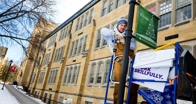 Sophomore Dan Vlourde removes a Christmas sign in order to put up a new branding sign on a lamp post outside John Roach Center for the Liberal Arts January 29, 2016.
