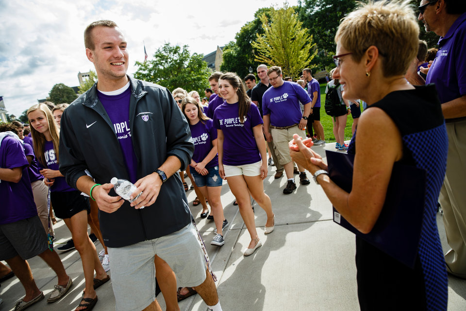 A student talks to president Julie Sullivan as he processes across the Lower Quad September 8, 2015 during the March Through the Arches, an annual ceremony where incoming freshmen are welcomed to campus.