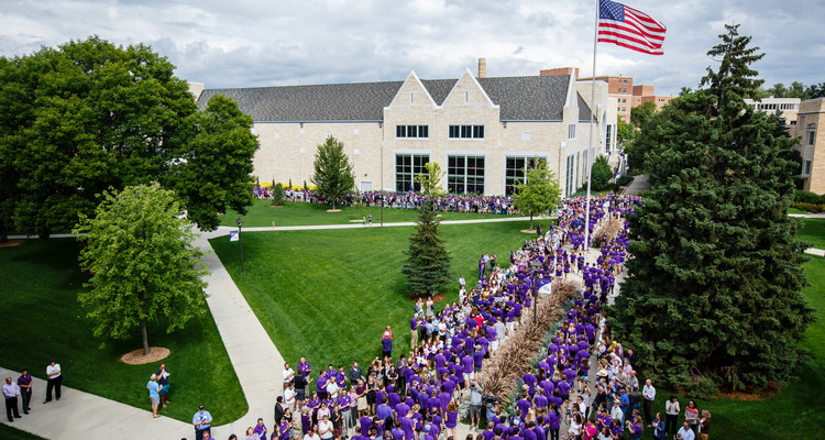 Incoming freshmen walk through the lower quad as faculty, staff and fellow students cheer them on during the March Through the Arches ceremony on September 8, 2015.
