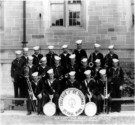 """U. S. Navy V-12 Band - Sept. 15th 1945. Group photograph of the Navy V-12 band. Aquinas Hall is in the background. Front row (l-r): Donald Borgett, """"Hap"""" Miller, Bruce Johnson, Dick Babock, Danny Braiovick. Middle row (l-r): Bill Caster, Jack McDougal, David Baird, Jim Stengel, Gaylon Kent, James Bowling, Dick Marietta. Back row (l-r): Robert Breidenbach, George Woodward, Dell O'Brien, Robert Person, John Wissler, Joseph Diroff(?) , Bud Jarvis, Jim Peterson, 07.02.02 V-12 Program on back of photograph.This image may not be reproduced for any reason without the express written consent of the Department of Special Collections, University of St. Thomas Libraries, 2115 Summit Avenue, Saint Paul, MN 55105; (651) 962 ? 5467 ; libweb@stthomas.edu."""