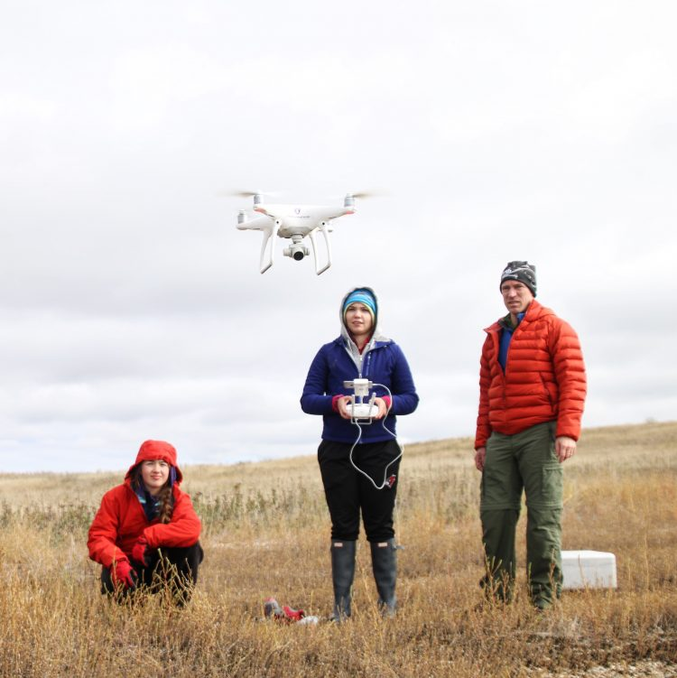 Students Shayna Thostenson and Emma Hodapp, and Dr. Paul Lorah launch the Department of Geography and Environmental Studies' conservation drone to map habitat for ground-nesting birds. Photo by Noelle Laske '20.