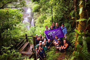 "First place, Tommies Abroad: Nick Hable, Costa Rica. ""Hidden Oasis in the Costa Rican Jungle: This photo shows our biology study abroad group holding the St. Thomas flag with a pristine waterfall in the background. This was in the middle of the Costa Rican jungle, next to Rara Avis, and we came across this after our four-hour hike into the jungle. This remote location is virtually untouched by humans, has a livelihood of animals and indigenous plants, and has little access to water and electricity. This location showed how simple life can be and it also changed our perspectives on how we view society in the United States."""