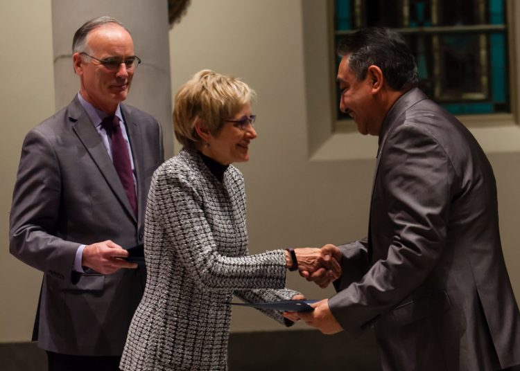 President Sullivan awarding a certificate to a graduate at St. Mary's Chapel for the Hispanic Lay Ministry Completion Ceremony on December 20, 2016.
