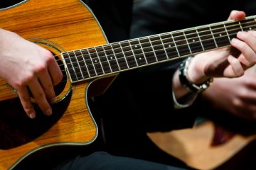 Hands on a guitar are show as the guitar ensemble performs during a dress rehearsal for the St. Thomas Christmas Concert December 6, 2015 at Orchestra Hall in Minneapolis.