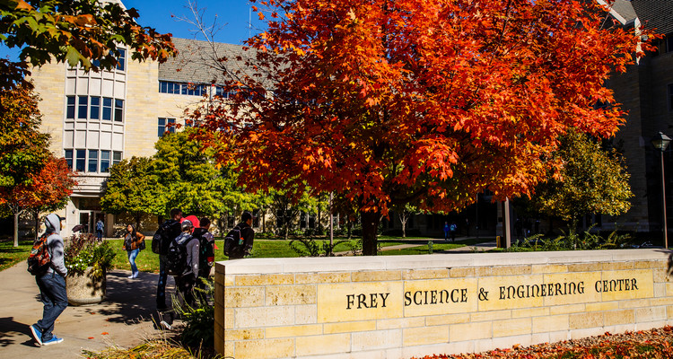 Students walk across south campus in front of O'Shaughnessy Science Hall in front of the Frey Science & Engineering Center sign on a sunny autumn day on October 13, 2016.