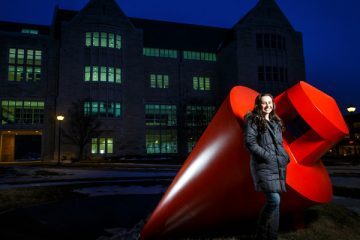 "Engineering major Lauren Vallez poses for a portrait next to ""The Plunge"" sculpture on south campus near the Frey Science and Engineering Building. Photo by Mark Brown."