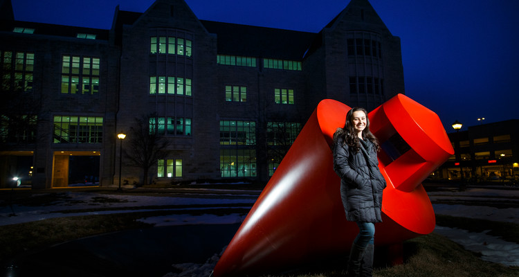 """Engineering major Lauren Vallez poses for a portrait next to """"The Plunge"""" sculpture on south campus near the Frey Science and Engineering Building. Photo by Mark Brown."""