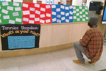 Student Riley Hare examines the comments on the Tommies Unspoken display.