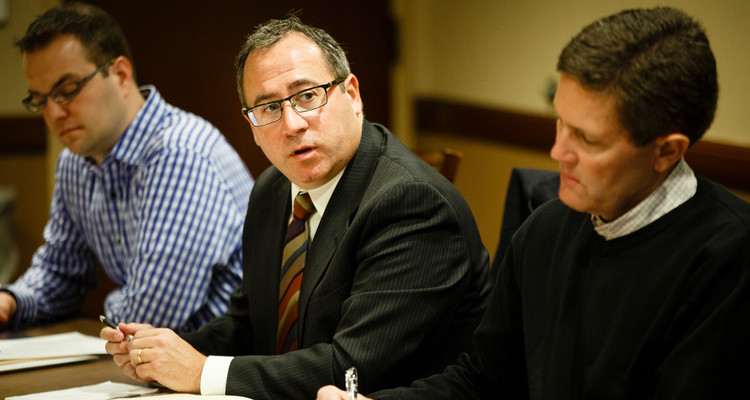 Board member Gino Lambo, middle, speaks during a Catholic Studies Advisory Board meeting at Terrence Murphy Hall on the Minneapolis campus on January 12, 2015. Board member Chris DuFresne is pictured to the far left and board member Joeseph Lahti is pictured to the right.