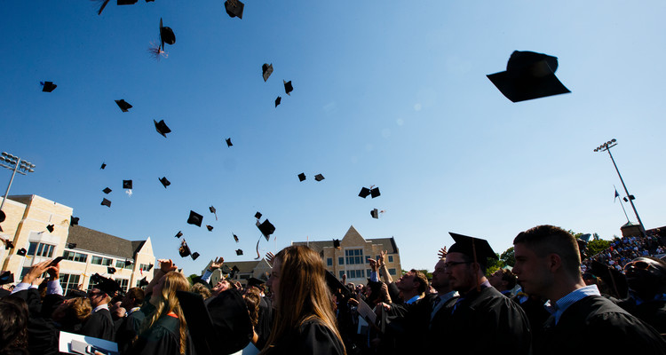 Students toss their caps in the air at the 2016 undergraduate commencement ceremony at O'Shaughnessy Stadium on May 21, 2016 in St. Paul.