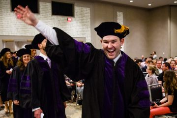 A student waves to family members during the School of Law Commencement ceremony May 13, 2017 at the Minneapolis Hilton.