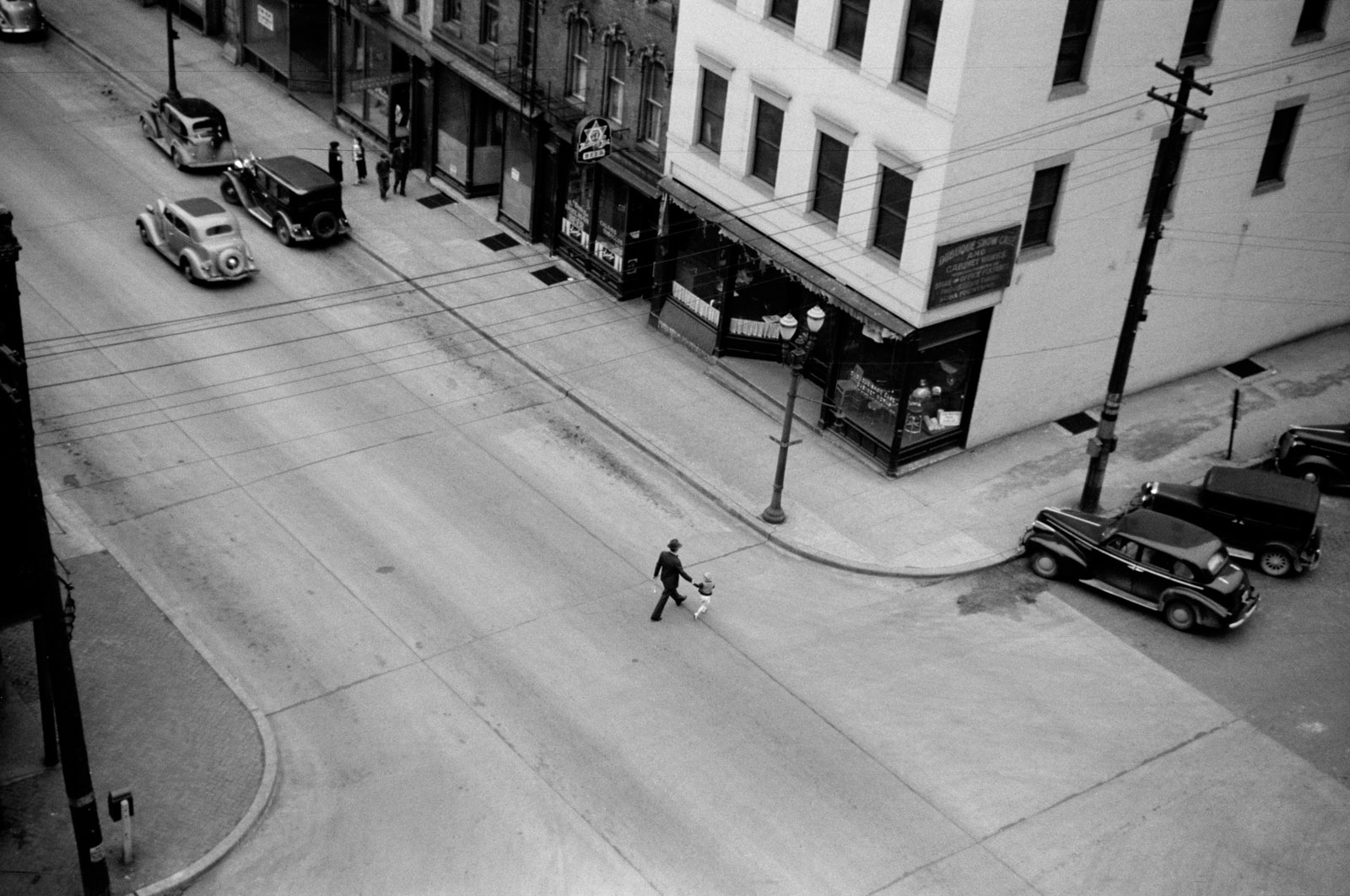 Man and boy crossing the street, Dubuque, Iowa 1940