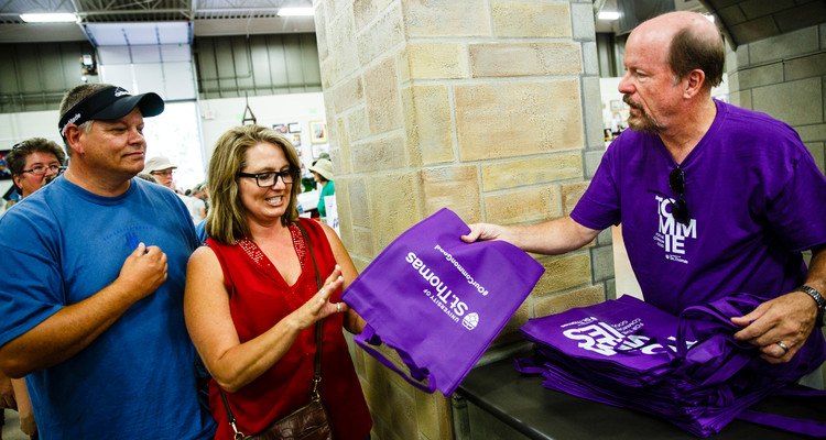 Doug Hennes, Vice President for Government Relations and Special Projects, hands out purple bags at the University of St. Thomas booth in the Education Building at the 2016 Minnesota State Fair on August 25, 2016.