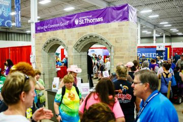 Fairgoers walk past at the University of St. Thomas booth with replica Arches in the Education Building at the 2016 Minnesota State Fair on August 25, 2016.