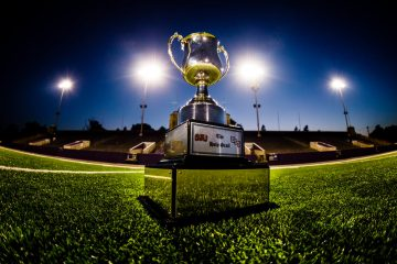 The Holy Grail trophy, the prize for winning the Tommie-Johnnie football game, is shown at night on the grass of Palmer Field inside O'Shaughnessy Stadium. Objects in the background and the reflection of the photographer have been removed in PhotoShop.