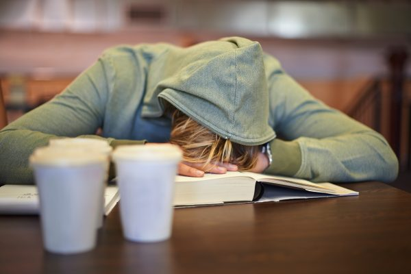 A student sleeps on the table while studying. The Center for College Sleep studies students' sleep and helps colleges and universities provide their students with better sleep.