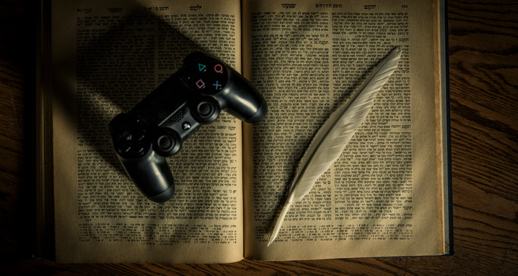 An Old Testament, a PlayStation 4 controller and a feather quill pen are shown April 12, 2017. Theology professor Corrine Carvalho and student Mike Best have done extensive work on the intersection of the Old Testament and Video Games. Taken for St. Thomas magazine.