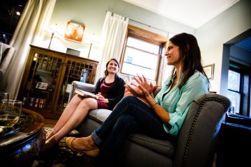 "Anna Knier (left) and Annie Mossbrugger discuss a book during a ""Well-Read Mom"" book club meeting August 31, 2017 at the St. Paul home of Beth Nelson."