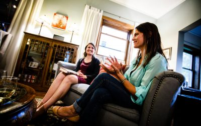 """Anna Knier (left) and Annie Mossbrugger discuss a book during a """"Well-Read Mom"""" book club meeting August 31, 2017 at the St. Paul home of Beth Nelson."""