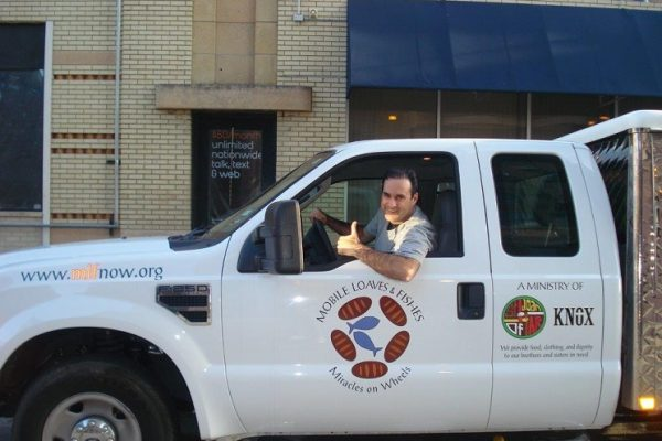 A man gives a thumbs up gesture from inside a Mobile Loaves and Fishes truck.