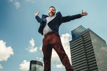 Joseph Johnson earned a BA in business (04) a Law degree (07) and an MBA (08) from the University of St. Thomas. Here Johnson jumps while posing for a portrait on the roof of the School of Law building with the skyscrapers of downtown Minneapolis in the background. He was photographed on August 2, 2017 for St. Thomas Lawyer Magazine.