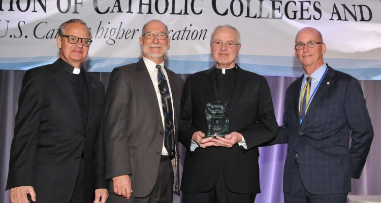 Father Dennis Dease, second from right, receives the Rev. Theodore Hesburgh Award from the Association of Catholic Colleges and Universities. To Dease's left are Monsignor Franklyn Casale, president of St. Thomas University in Miami, and Michael Galligan-Stierle, president of the ACCU. On the right is Thomas Mengler, president of St. Mary's University in San Antonio, new board chair of the ACCU and former University of St. Thomas School of Law dean.