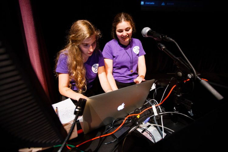 Emily Meuer (Computer Science) left, and Amanda Tenhoff (Mechanical Engineering), right, work on a laptop during a collaborative multimedia performance with the University of St. Thomas Playful Learning Lab and Twin Cities based sining group Cantus at the Science Museum of Minnesota in downtown St. Paul on July 8, 2016.