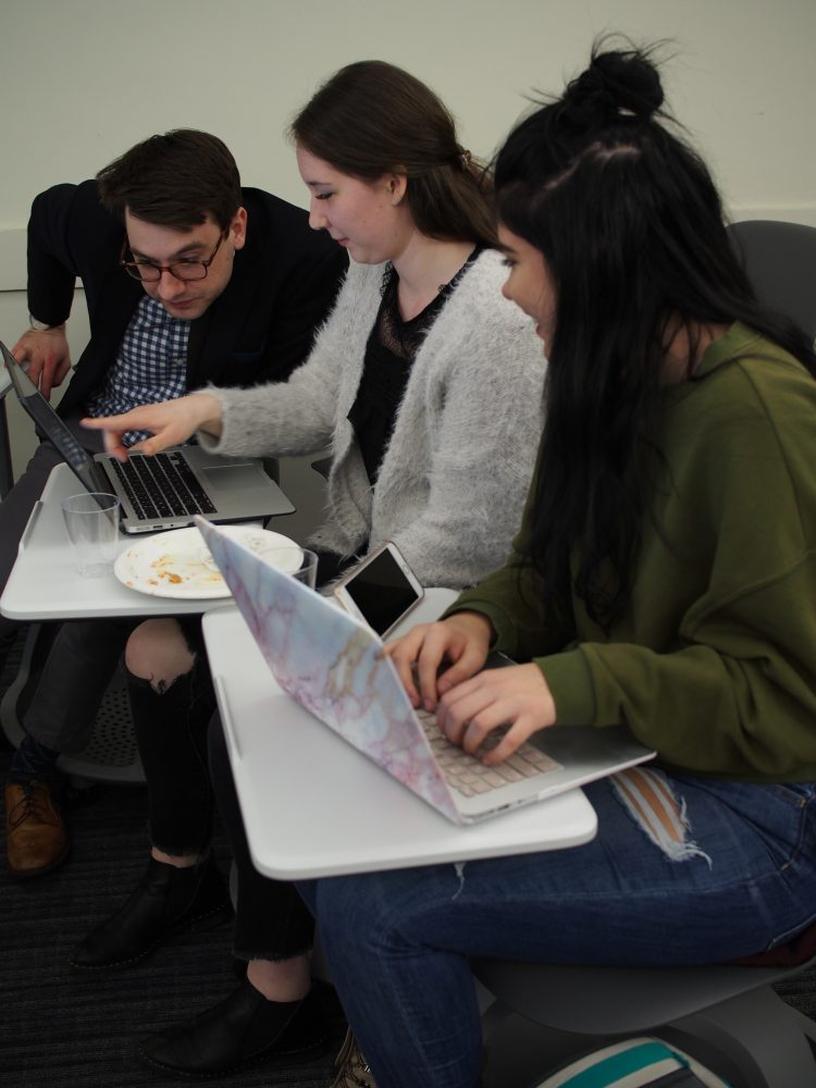 """History faculty Michael Blaakman works with students during St. Thomas' """"Transcribe-a-thon"""" on March 13."""