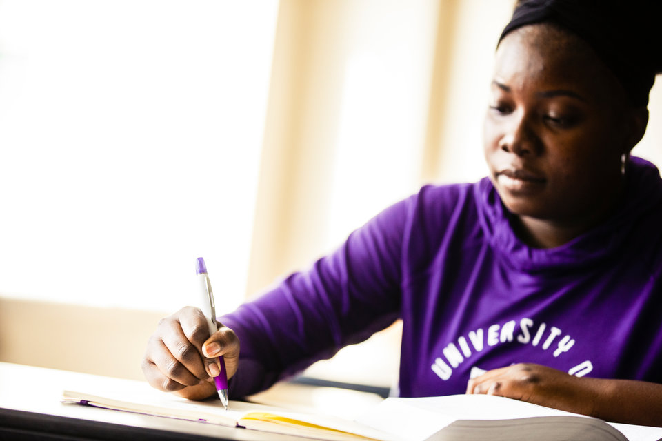 Dougherty Family College student Fanta Keita writes in a notebook during staged scenes September 15, 2017 in Terrence Murphy Hall.
