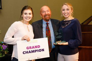 St. Thomas undergraduate students Jackie Page (left) and Megan Sharkus (right) stand with Richard Schulze on April 14 at e-Fest after being named grand champion for their business, ExpressionMed.